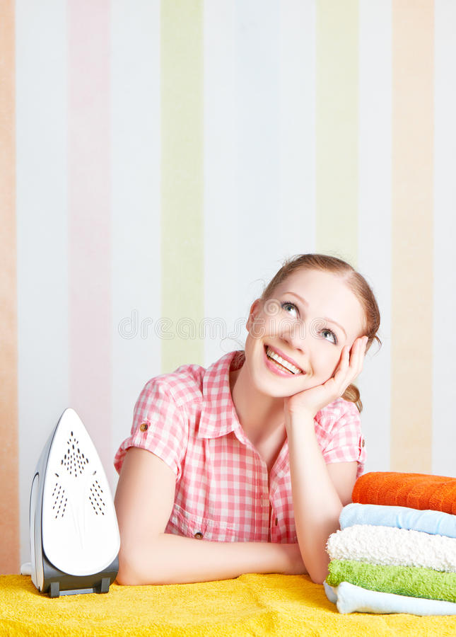 Housewife dreamy woman with iron engaged in domestic work stock photos