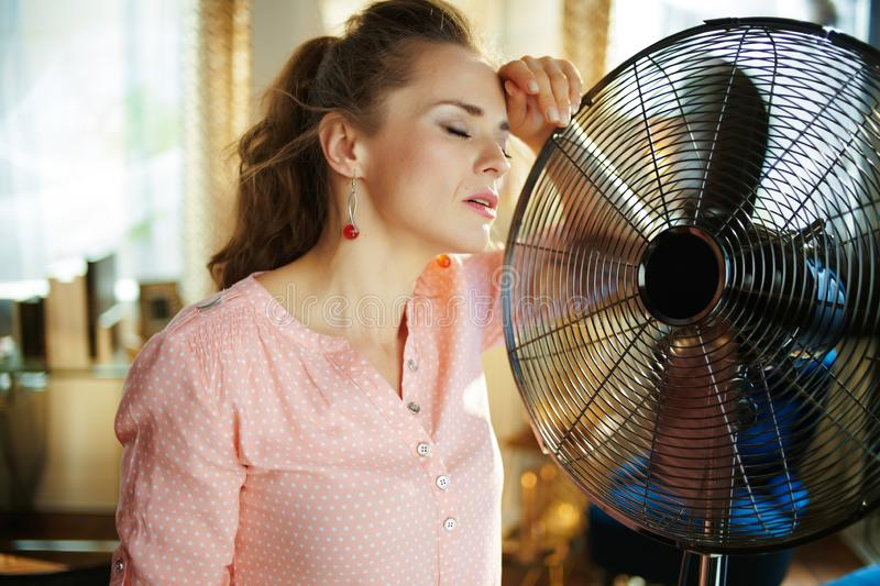 Housewife enjoying fresh air in front of working fan stock images