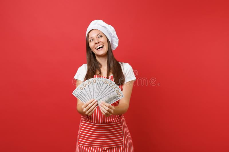 Housewife female chef cook baker in striped apron, white t-shirt, toque chefs hat isolated on red wall background. Happy. Woman holding lots of dollars stock photography