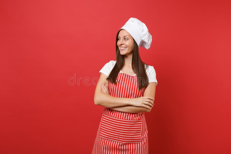 Housewife female chef cook or baker in striped apron, white t-shirt, toque chefs hat isolated on red wall background stock photo