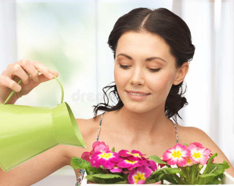 Housewife with flower in pot and watering can. Lovely housewife with flower in pot and watering can royalty free stock photos