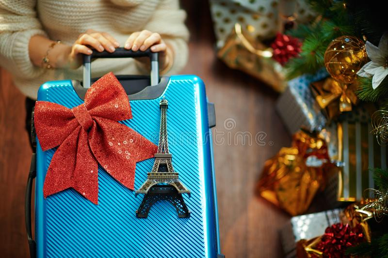 Woman with travel suitcase and Eiffel tower souvenir. Housewife in gold sequin skirt and white sweater with blue travel suitcase and Eiffel tower souvenir under stock image