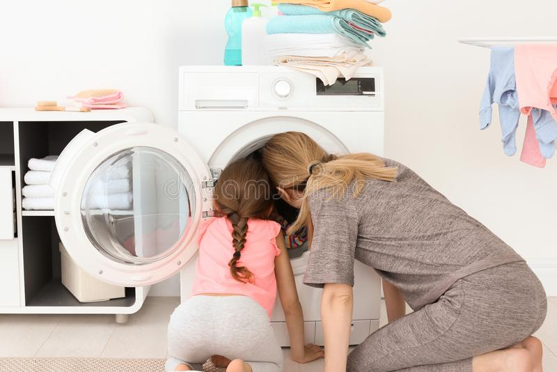Housewife with her little daughter doing laundry at home stock image