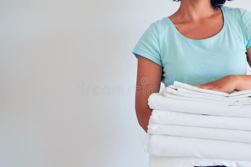Housewife holding a stack of washed bed linen. washing clothes and linen, bleaching of white things royalty free stock photos