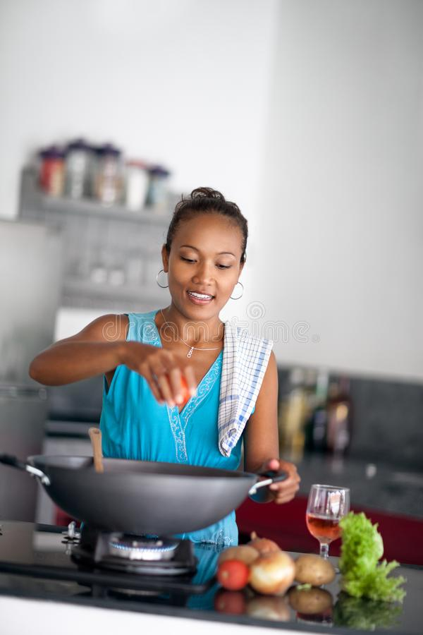 Housewife in kitchen squeezes tomato in meal royalty free stock image
