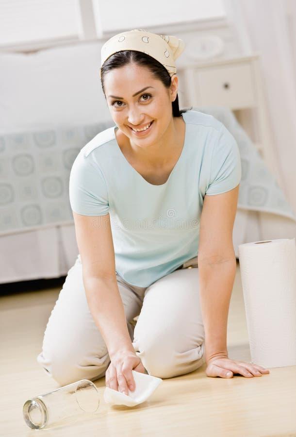 Housewife kneeling in bedroom wiping up spill