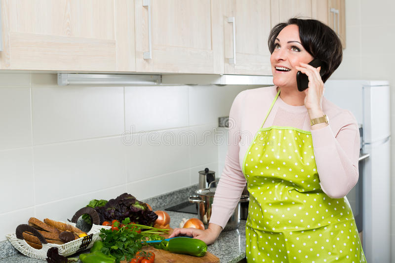 Housewife with phone at kitchen. Cheerful brunette woman chatting with somebody on phone as cooking dinner stock photo