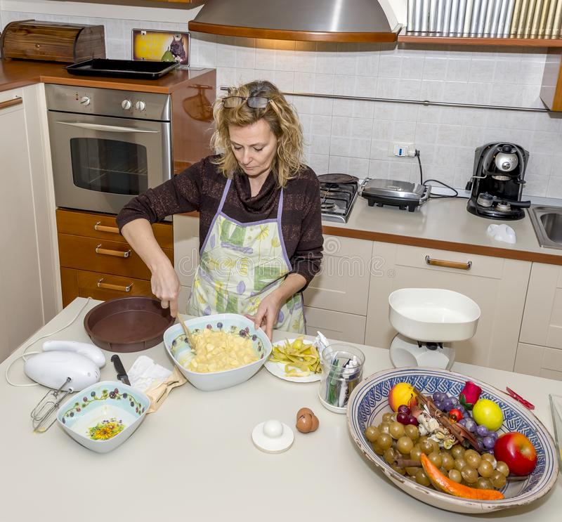 Housewife prepares an apple dessert in a messy kitchen royalty free stock photos