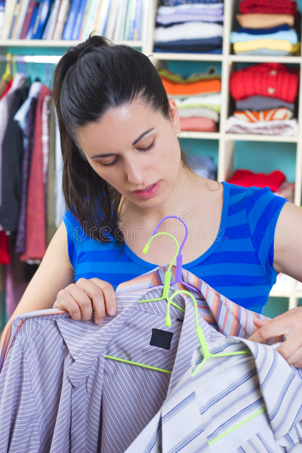 Housewife putting clothes on available space. Hanger, shelves stock image