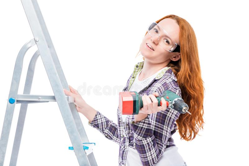 housewife during repairs, portrait on a ladder with tools royalty free stock photo