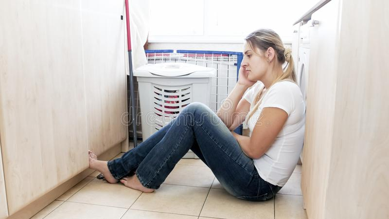 Young housewife resting on floor at laundry room after housework. Housewife resting on floor at laundry room after housework stock photos