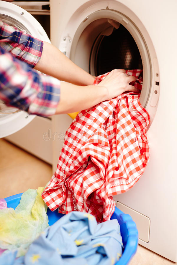 Housewife's hands putting the laundry into the washing machine royalty free stock image