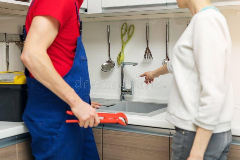 Housewife showing broken water tap to plumber royalty free stock photos