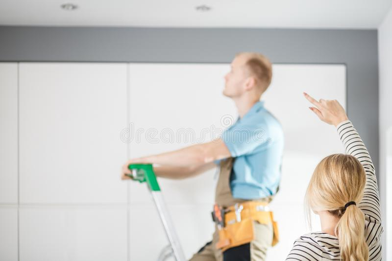 Housewife showing fault to electrician stock photography