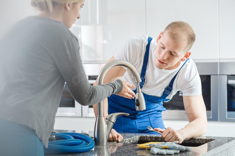 Housewife showing glitch to plumber stock photography