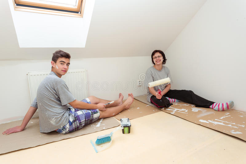 Housewife with son painting wall to white royalty free stock images