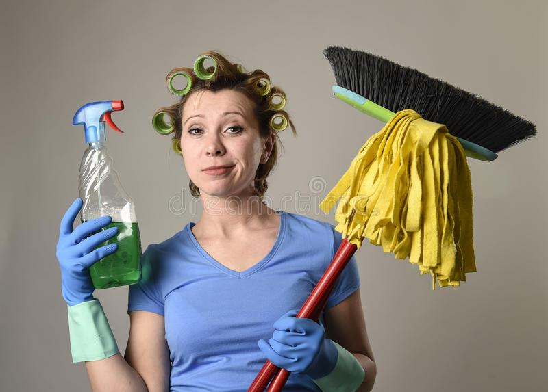 Housewife stereotype hair rollers and washing gloves holding mop broom and detergent spray bottle. Young red hair woman in housewife stereotype hair rollers and stock photography
