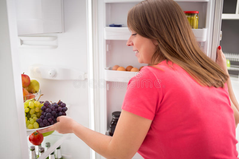 Housewife take plate full of grapes from fridge royalty free stock photography