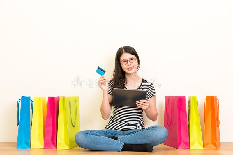 Housewife using credit card to shopping online. Young housewife using credit card to shopping online at home through e-commerce systems paying by digital tablet stock images