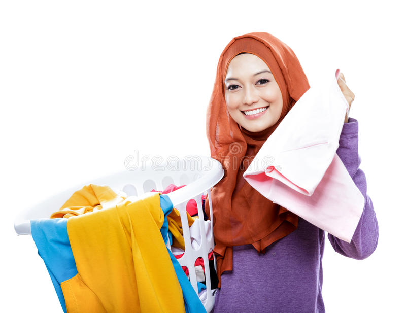 Housewife wearing hijab carrying laundry basket and pick up one. Portrait of housewife wearing hijab carrying laundry basket and pick up one clothes isolated on royalty free stock photography