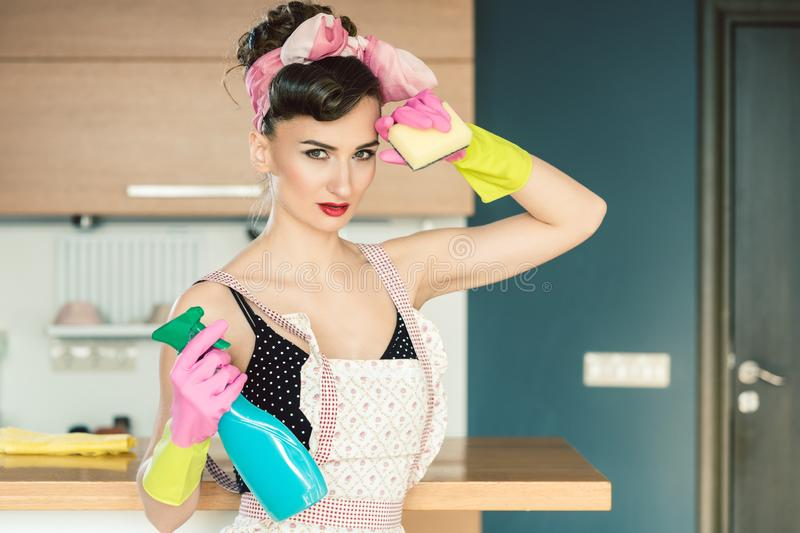 Housewife woman in retro outfit attempting to clean the kitchen royalty free stock images