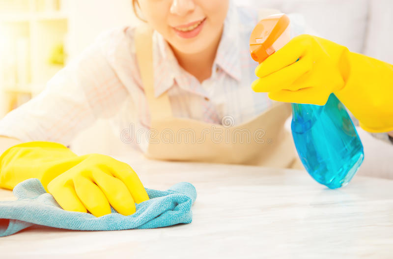 Housewife in yellow gloves cleaning table royalty free stock photo