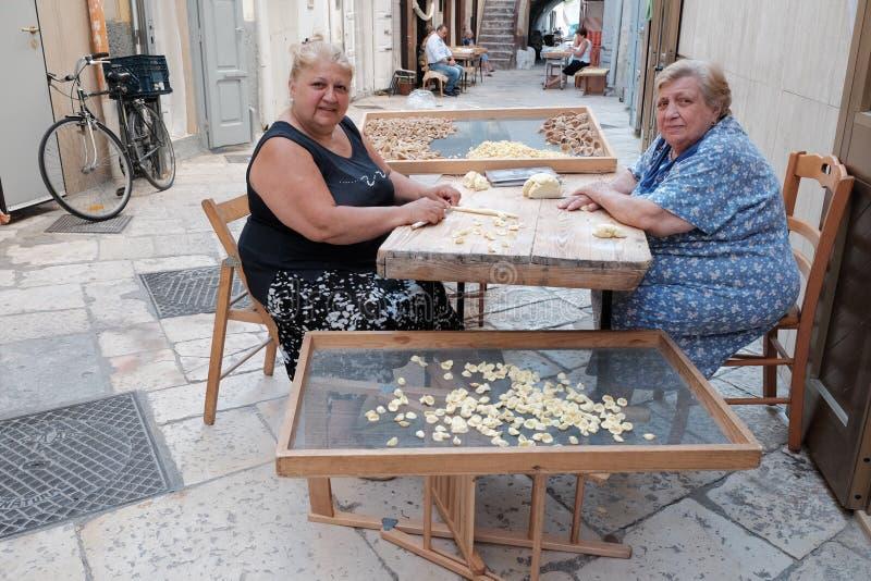 Housewifes que hace las pastas frescas en Bari vieja, Italia fotografía de archivo