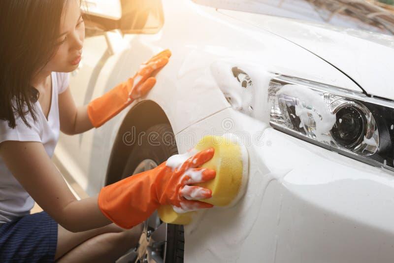Housewilfe houdt de spons in hand en poetst de auto op Selectieve nadruk royalty-vrije stock afbeelding