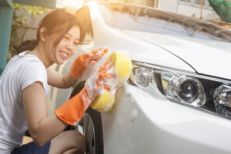 Housewilfe houdt de spons in hand en poetst de auto op Selectieve nadruk stock foto