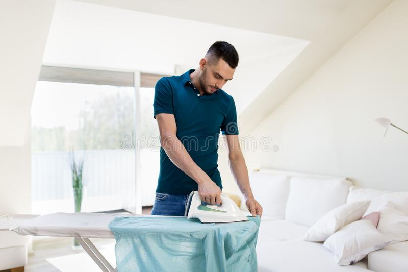 Man ironing shirt by iron at home. Housework and household concept - man ironing shirt on iron board at home stock photo