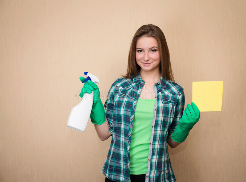 Housework and housekeeping concept. Young woman with cleaning sp stock image