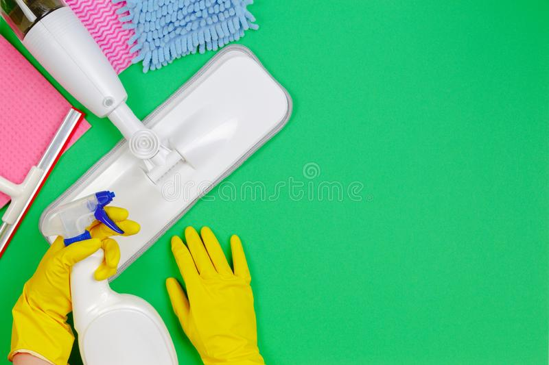 Housework, housekeeping, household, cleaning service concept. Cleaning spray mop, rags, sponges on green and woman hands. In yellow rubber gloves with detergent stock image