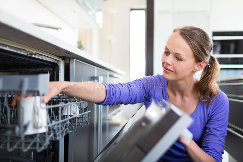 Housework. Young woman putting dishes in the dishwasher stock photos