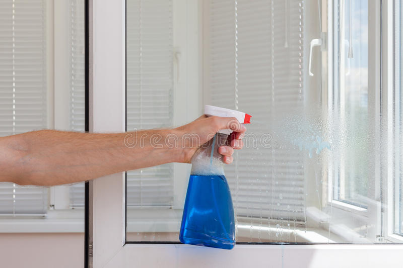 Houseworker clean plastic pvc windows with detergent. Houseworker clean plastic pvc windows with detergent royalty free stock image