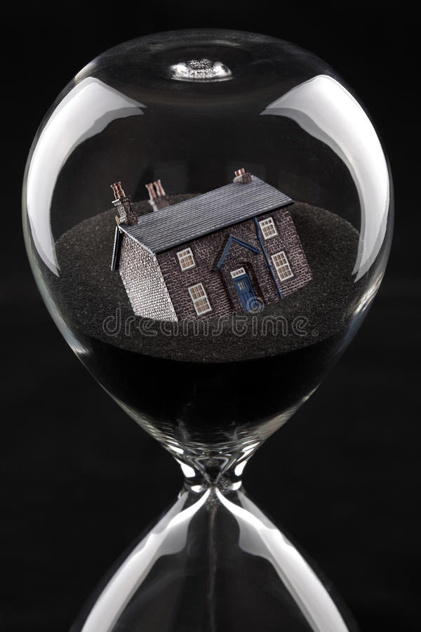 Housing market collapse. Hourglass with house sinking into sand concept for housing market recession or housing difficulties stock photography