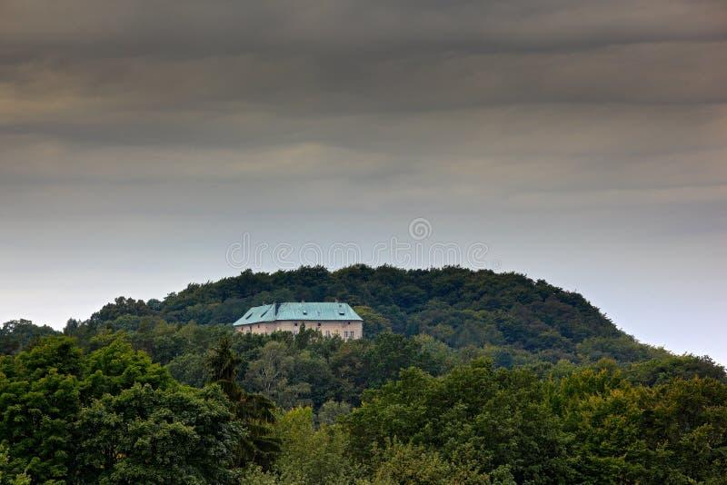 Houska城堡在捷克,中波希米亚州,欧洲 陈述世袭的社会等级,在绿色森林,深灰云彩里hiden lan的塔房子 免版税库存图片