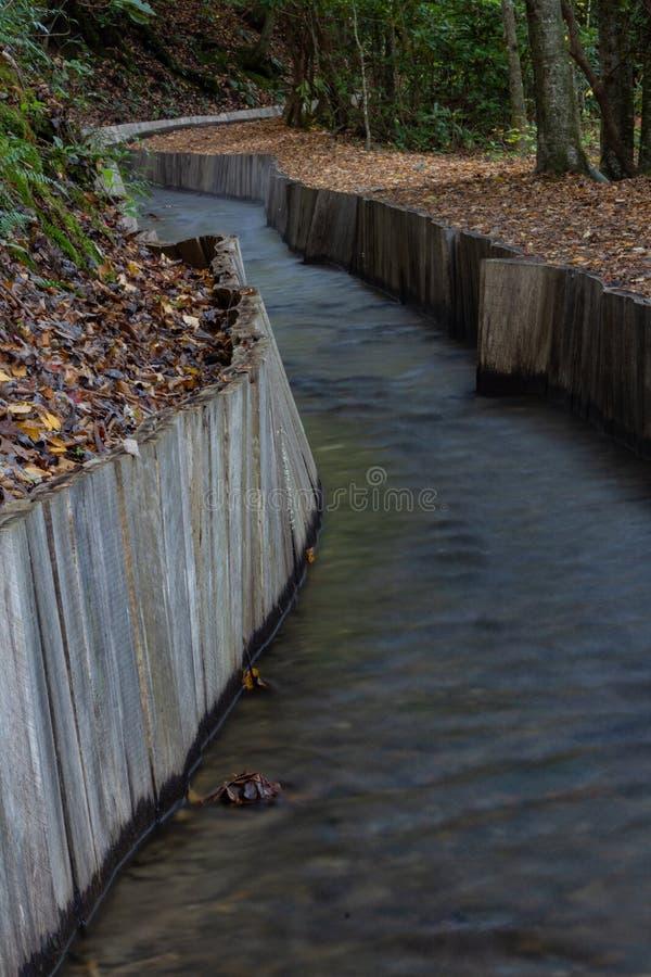 Hout ommuurde sluis die door bebost gebied winden die tot een oude molen leiden stock afbeeldingen
