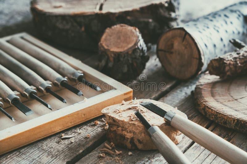 Houtbewerkingshulpmiddelen voor houtsnijwerk en bomenbesnoeiingen op houten werkbank stock foto