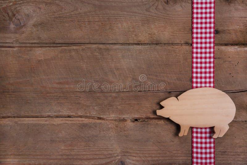 Houten achtergrond met goed gelukvarken op geruit lint of adve stock foto