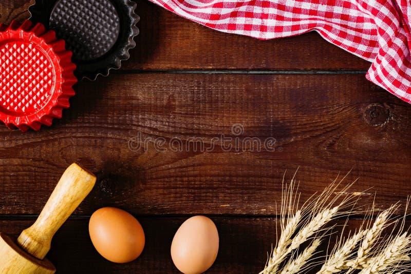 Houten achtergrond met het bakken van ingrediënten en het koken van steunen royalty-vrije stock afbeelding