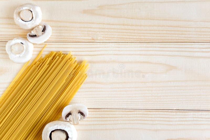 Houten achtergrond met spaghetti en paddestoelen Voedselachtergrond het Italiaans Ruwe champignons en deegwaren op een houten ach stock afbeelding