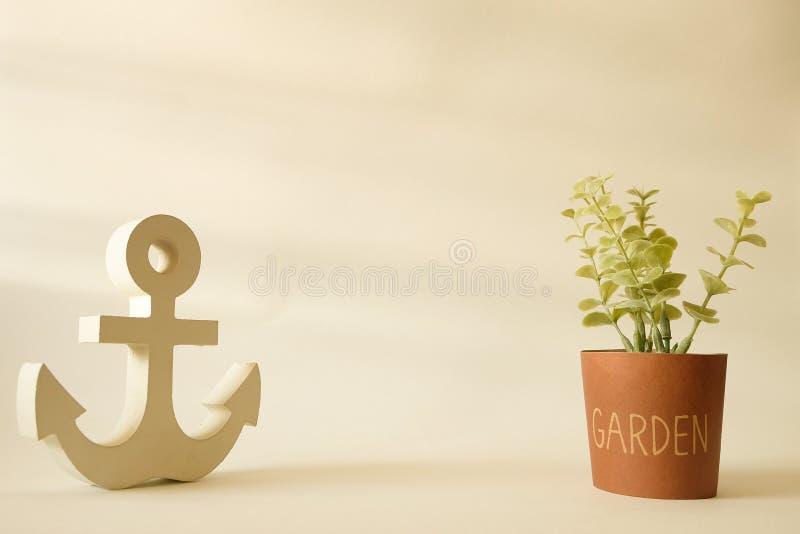 Houten anker in minimalistische stijl met kleine boom op pottenachtergrond stock afbeeldingen