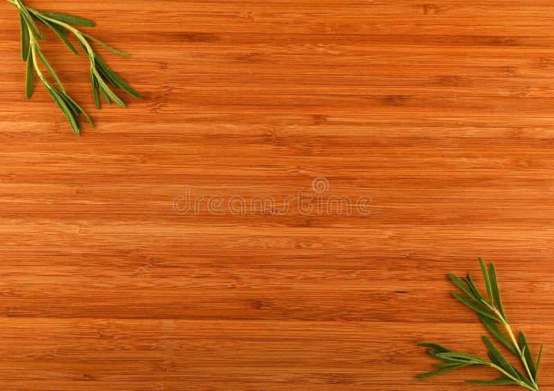 Houten bamboe scherpe raad met rozemarijnbladeren stock foto
