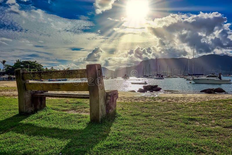Houten bank en steen door het overzees bij ongelooflijke zonsondergang met zonstralen die tussen wolken en boten op de achtergron royalty-vrije stock fotografie