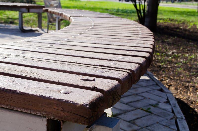 Houten bank in het park Bank voor rust Steeg in de stad Plaatsen voor rust Groene parken in de stad Openbare ruimte Een plaats aa royalty-vrije stock fotografie