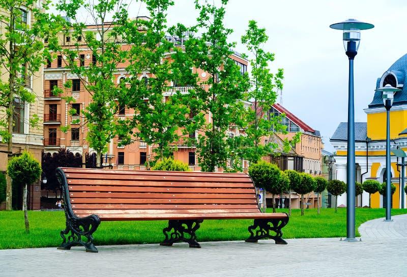 Houten bank in het stadspark tegen de achtergrond van stedelijke gebouwen, concept reis en recreatie, de Oekraïne, Kiev, n royalty-vrije stock foto's