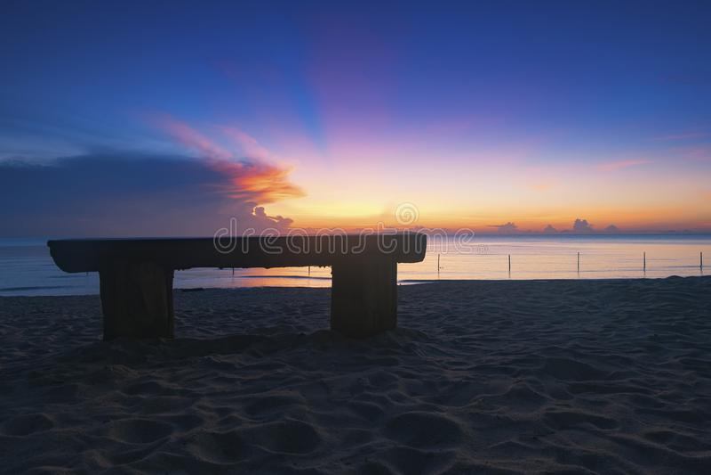 Houten bank over mooi tropisch strand en magische schemering royalty-vrije stock afbeelding