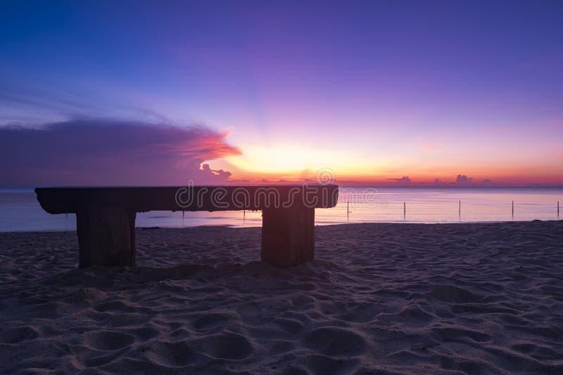 Houten bank over mooi tropisch strand en magische schemering stock foto