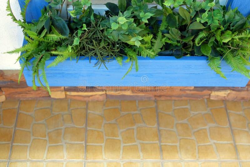Houten bank voor rust onder het venster Bloemen door het venster royalty-vrije stock afbeeldingen