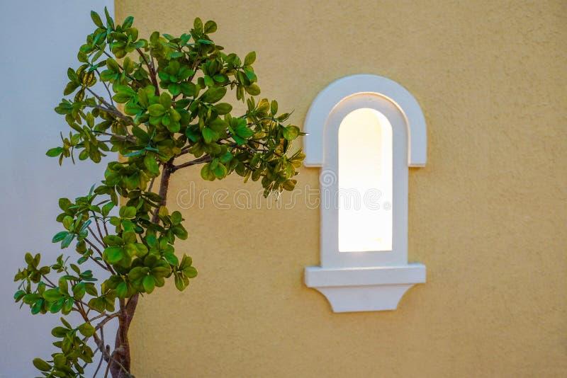 Houten bank voor rust onder het venster Bloemen door het venster royalty-vrije stock afbeelding